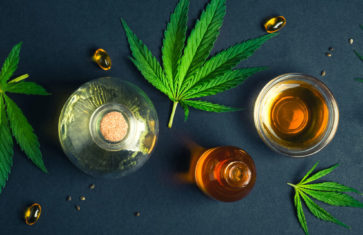 Medical CBD oil on black trendy background with cannabis leaves.