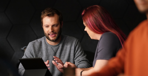 Two people meeting and looking at a tablet