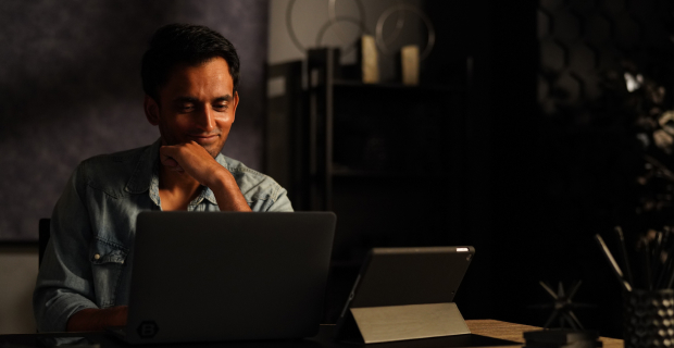 Man looking at a laptop screen in his office